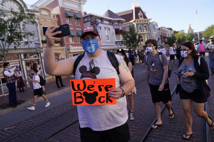 FILE - In this Friday, April 30, 2021, file photo, visitors walk down Main Street USA at Disneyland in Anaheim, Calif. California, the first state in America to put in place a coronavirus lockdown, is now turning a page on the pandemic. Most of California's coronavirus restrictions will disappear Tuesday, June 15, 2021. (AP Photo/Jae Hong, File)