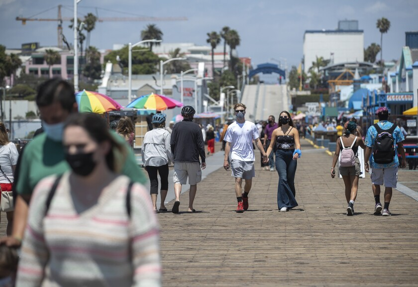 People wear protective face coverings during their strolls Monday on the Santa Monica Pier.