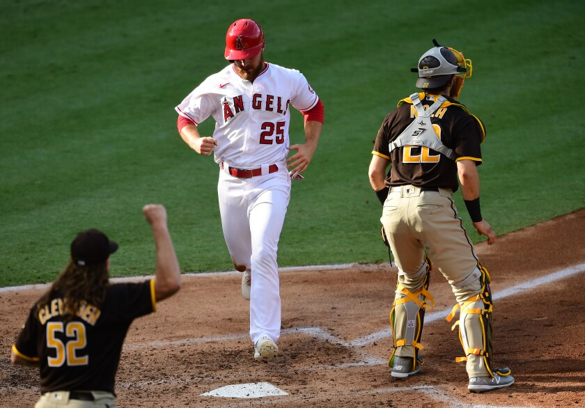 Angels' Jared Walsh scores in third inning Thursday at Angel Stadium as catcher Austin Nola and pitcher Mike Clevinger watch.