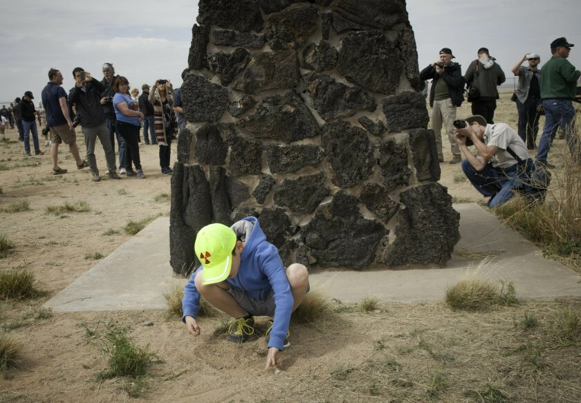 Eight-year-old Josiah Fidel, from Albuquerque, N. M., plays in the dirt next to the obelisk commemorating the first atomic bomb test at the Trinity Site at White Sands Missile Range in New Mexico as other visitors to the site take photographs on April 4, 2015. The White Sands Missile Range opened t