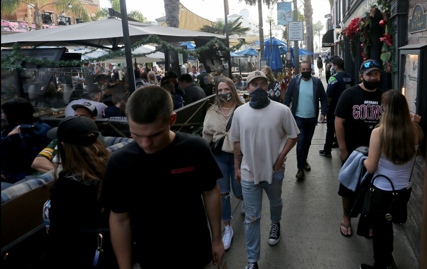 Shoppers and diners, both masked and unmasked, crowd Main Street in Huntington Beach on Dec. 6, 2020.