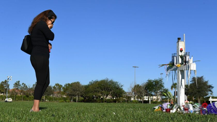 A woman cries as she visits a makeshift memorial for the victims of the Marjory Stoneman Douglas High School shooting victims in Parkland, Fla. on February 16.