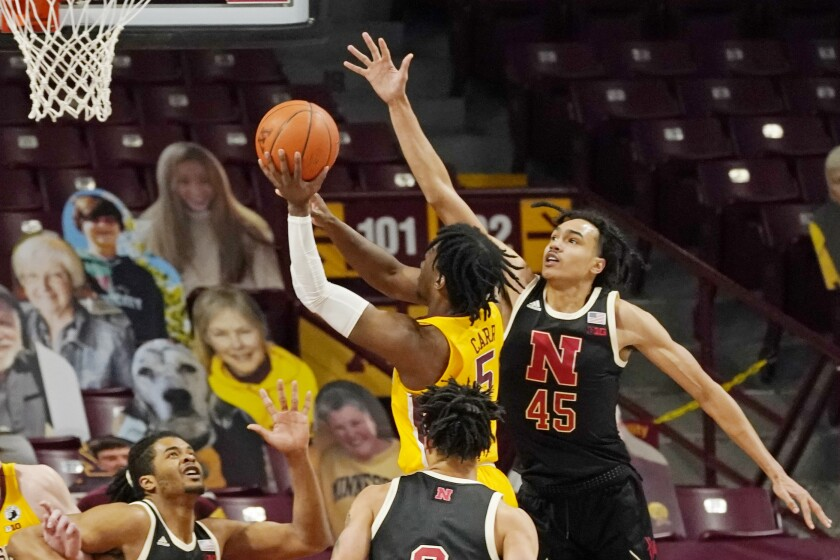 Minnesota's Marcus Carr (5) shoots as Nebraska's Dalano Banton (45) defends in the second half of an NCAA college basketball game, Monday, Feb. 8, 2021, in Minneapolis. Carr led Minnesota with 21 points. (AP Photo/Jim Mone)