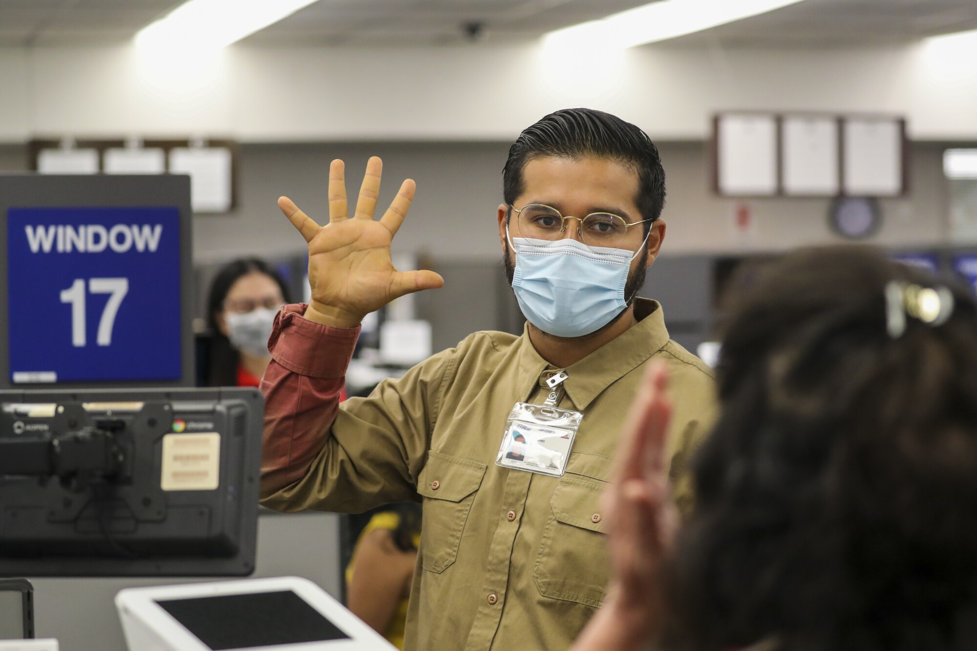 A DMV worker wearing a mask and glasses raises his hand with his fingers spread apart while administering a vision test