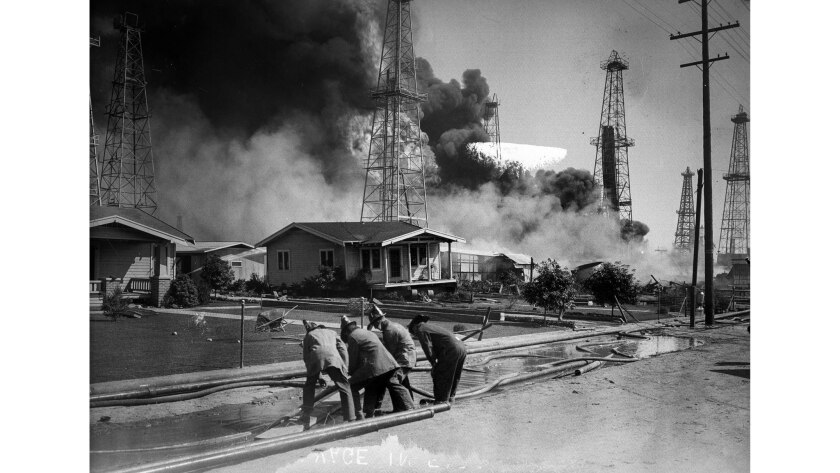 Sept. 19, 1928: Firefighters lay hoses to protect homes from an oil well fire in Santa Fe Springs.