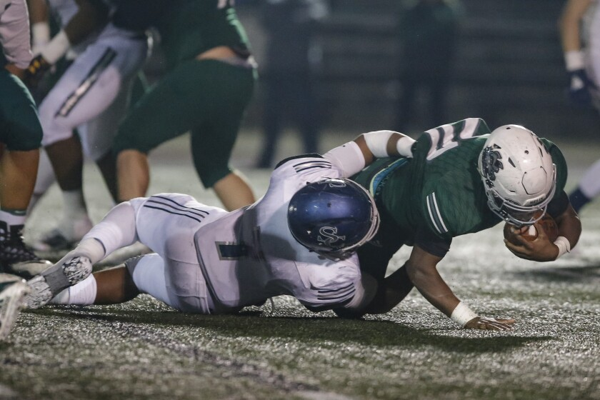 Sierra Canyon linebacker Drue Watts tackles Helix running back Christian Washington in Friday's Division 1-AA Southern California Regional playoff game. The Trailblazers defeated the Highlanders 38-20.