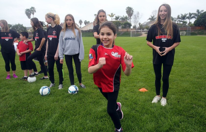 Champions League participant Sophia Flore, 8, takes parts in a soccer drill on Saturday at Ada Harris Elementary School in Cardiff. The League was created to for youth with special needs.