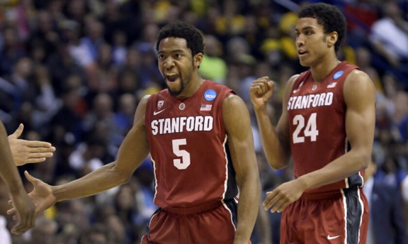 Stanford's Chasson Randle, left, and Josh Huestis celebrate during the second half of their 60-57 upset win over Kansas in the third round of the NCAA tournament Sunday.