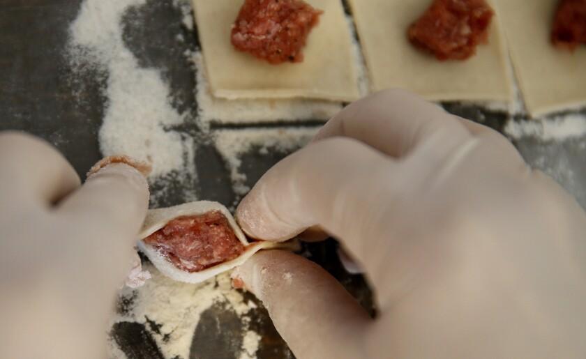 Evelina Yegiazaryan pinches the dough around the meat filling to make the manti.