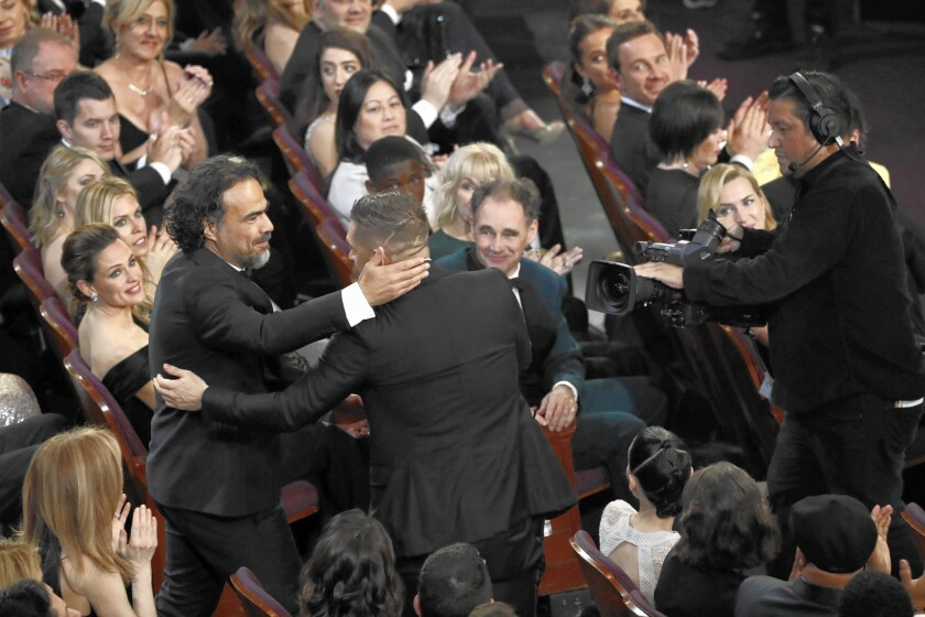 """The Revenant"" director Alejandro G. Inarritu, left, is embraced by the film's supporting actor nominee, Tom Hardy, at the Oscars. Inarritu's win was his second straight in the director category. He won last year for ""Birdman."""