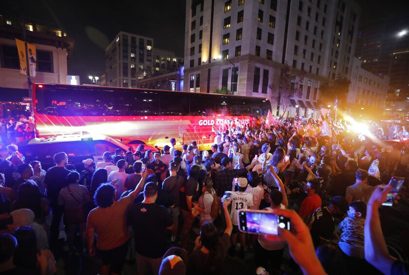 Thousands of fans surround the Padres team bus Friday as it leaves Petco Park after winning the NL Wild Card Series.