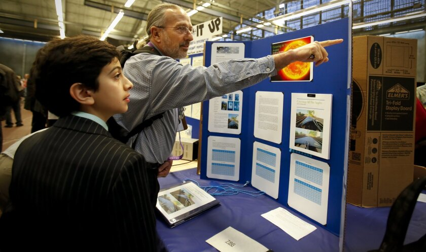 Pasha Bouzarjomehri, left, a student at The Rhoades School in Encinitas explains his project on making solar panels more efficient to Joe  Ippolito, a project engineer and judge during the annual Greater San Diego Science and Engineering Fair at the Balboa Park Activity Center.