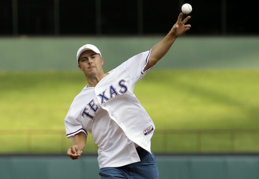 PGA golfer Jordan Spieth throws the first pitch before a baseball game between the Seattle Mariners and Texas Rangers in Arlington, Texas, Tuesday, Aug. 18, 2015. (AP Photo/LM Otero)