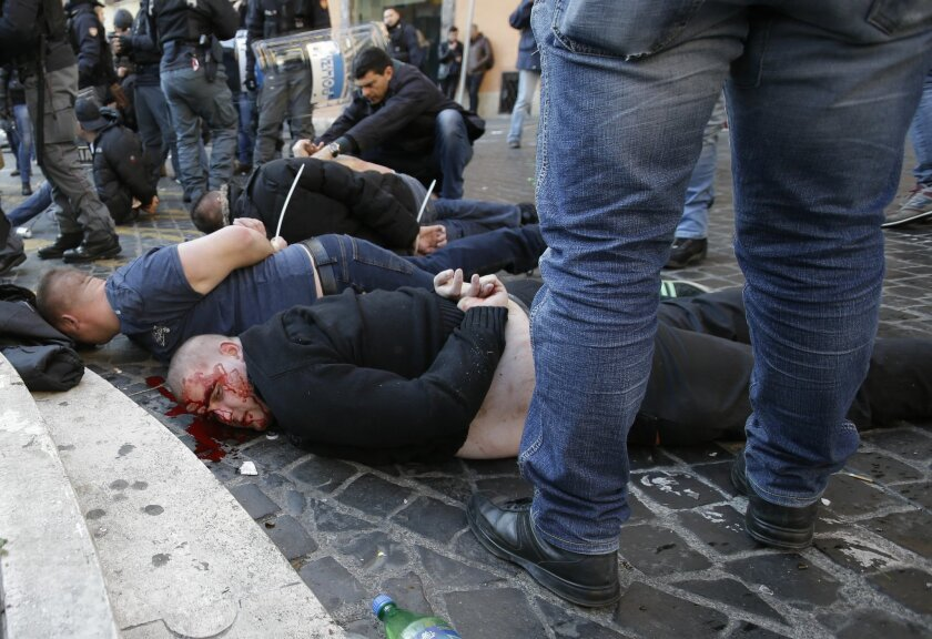 FILE - In this Thursday, Feb. 19, 2015 file photo, an injured Feyenoord fan lies on the ground after being arrested with others during clashes with Italian policemen at the Spanish steps prior to the start of the Europa League soccer match between Roma and Feyenoord in Rome. (AP Photo/Gregorio Borgia, File)