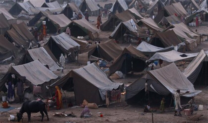 In this photo taken on Sept. 22, 2010, people stand outside their tents at a camp for those displaced by floods in Sukkur, southern Pakistan. About 8 million remain homeless following the country's worst flooding in living memory, many staying in hundreds of relief camps that have sprung up to house them. (AP Photo/Aaron Favila)