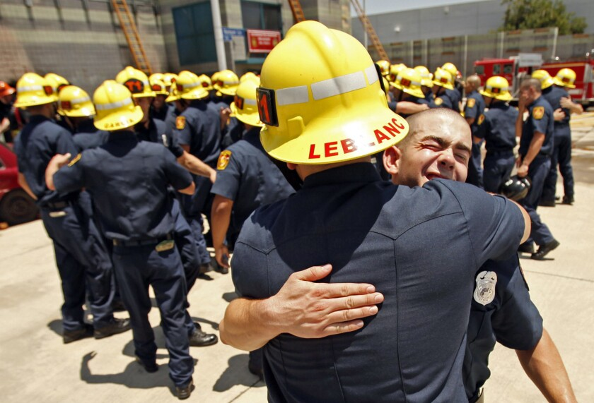 Daniel Balzano, right, gets a hug from Matthew LeBlanc as 58 recruits of the Los Angeles Fire Department celebrate following the recruit graduation ceremony on June 12. More than 10,000 applicants have applied for the next round of LAFD hiring.