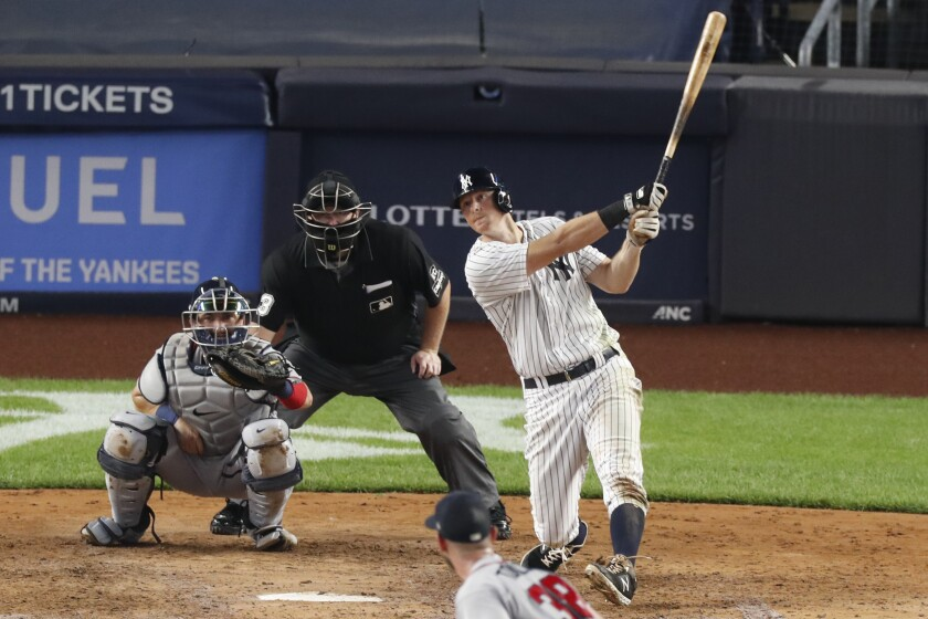 New York Yankees DJ LeMahieu, right, hits an RBI single during the fifth inning of a baseball game against the Atlanta Braves, Wednesday, Aug. 12, 2020, in New York. Braves catcher Travis d'Arnaud, left, and home plate umpire Todd Ticheonor watch. Braves pitcher Josh Tomlin is on the mound (AP Photo/Kathy Willens)