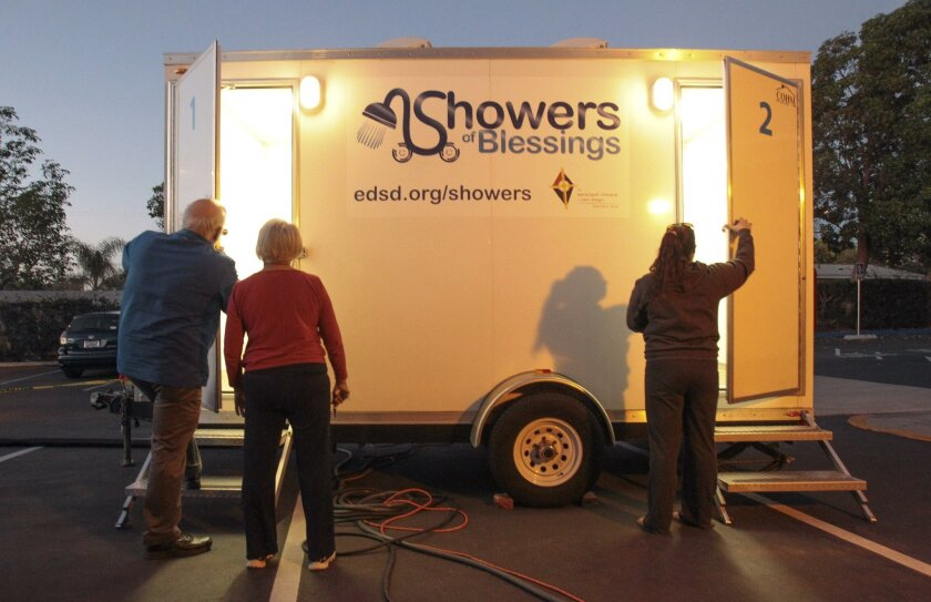 Rotational shelter coordinator Bill Zucconi, left, his daughter and volunteer Laura Zucconi, right, and church shelter coordinator Linda Counts unlock the doors to the two shower trailer used by people staying in the temporary winter shelter at St. Andrew's Episcopal Church in Encinitas on Wednesda