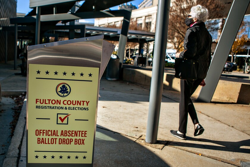 A voter arrives at the Buckhead library in Atlanta on the first day of in-person early voting Dec. 14, 2020.