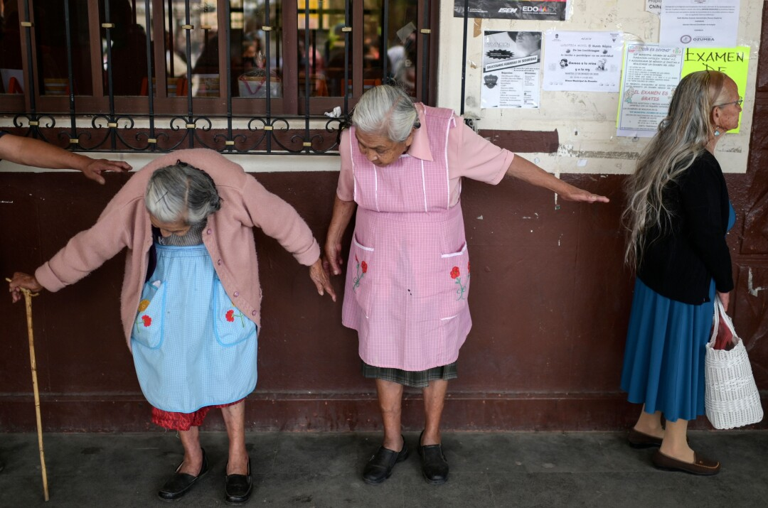 MEXICO: Older women keep a distance as they wait to enroll in government social aid programs in downtown Ozumba, Mexico, during the coronavirus outbreak.