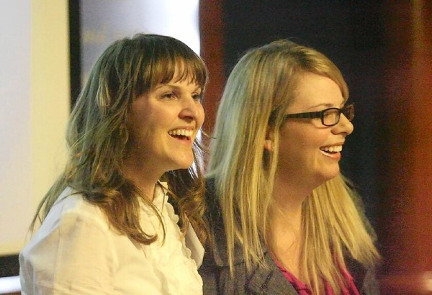 Filmmakers Ann-Caryn Cleveland, left, Olivia Klaus share a light moment as they speak at the 90 Days of Vanguard event at Vanguard University on Thursday. The two award-winning documentary filmmakers are alumni of Vanguard who also teach at the school.