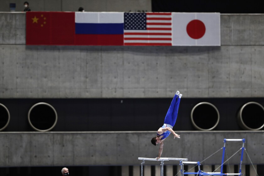 Dimitrii Lankin of Russia competes in the parallel bars of an international gymnastics meet in Tokyo on Sunday, Nov. 8, 2020. Gymnasts from four countries of China, Russia, U.S. and Japan performed in the meet at Yoyogi National Stadium First Gymnasium, a venue planned to be used in the Tokyo 2020 Olympics in the summer 2021. (AP Photo/Hiro Komae)