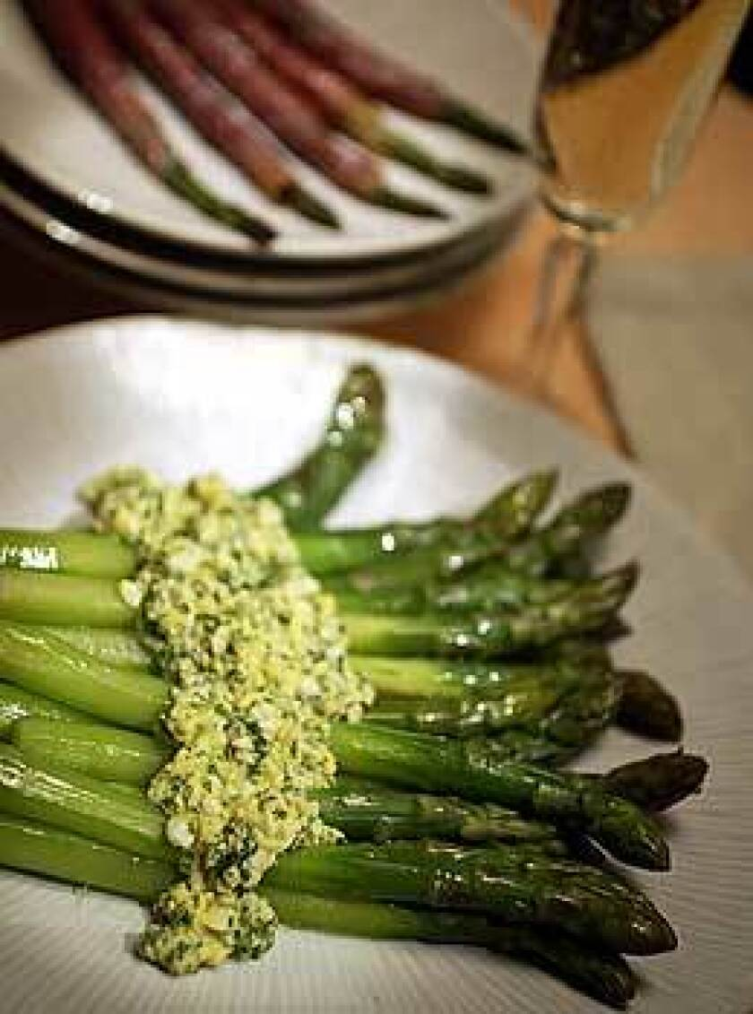 Thick asparagus are best peeled and sauced. Here they're served with sauce mimosa, a vinaigrette enriched with hard-boiled eggs. In the background, medium spears are wrapped in prosciutto and roasted. Thin spears are best in dishes with other ingredients.