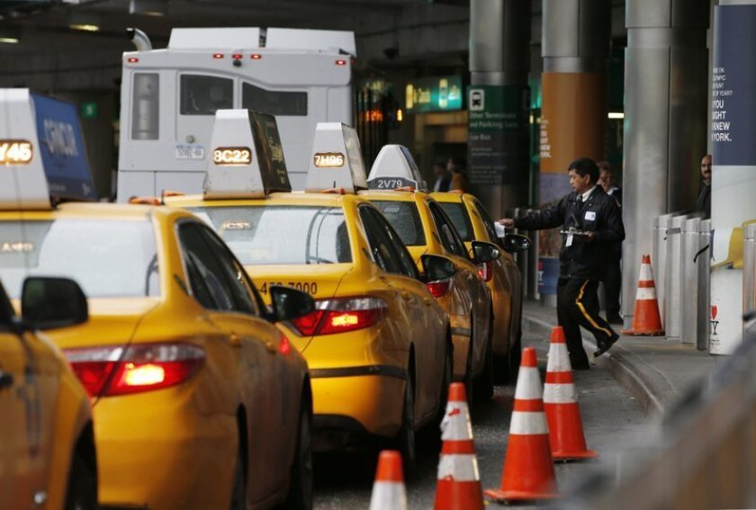 In this Wednesday, May 4, 2016, photo, a taxi dispatcher hands a piece of paper to a driver as other taxis line up awaiting passengers outside the arrivals area of a terminal at LaGuardia Airport, in New York. Airports across the country add surcharges of up to $5 a ride, typically passed directly on to travelers, for trips originating at their curbs. There are similar charges for limousine, Uber and Lyft drivers as well as shuttle buses for hotels, car rental companies and off-airport parking lots.