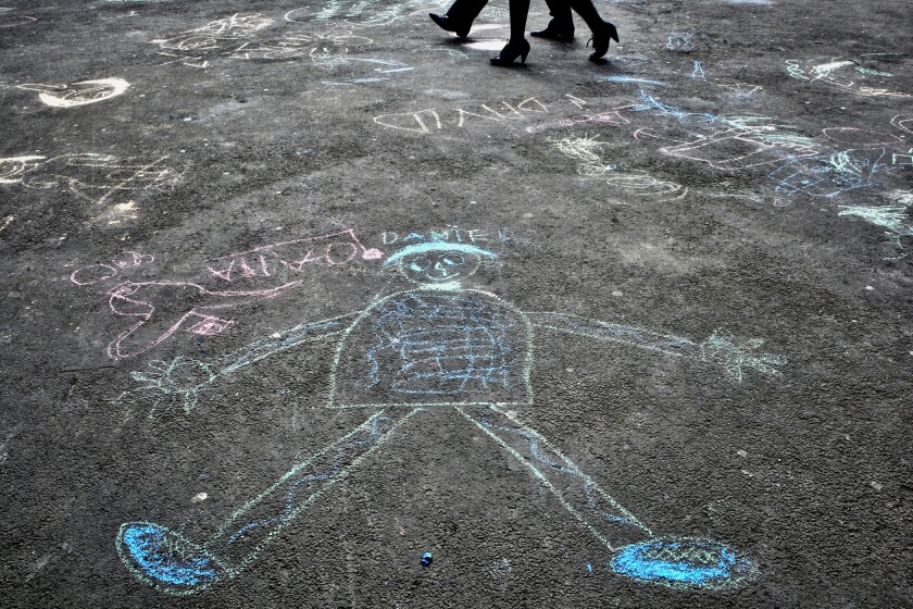FILE - In this Saturday, April 2, 2011 file photo, pedestrians walk past drawings by autistic children after an event in Bucharest, Romania to mark World Autism Awareness Day. According to a U.S. study published in the New England Journal of Medicine on Wednesday, Oct. 13, 2021, children with autism didn't benefit from an experimental therapy using the hormone oxytocin, thought to promote social bonding. (AP Photo/Vadim Ghirda)