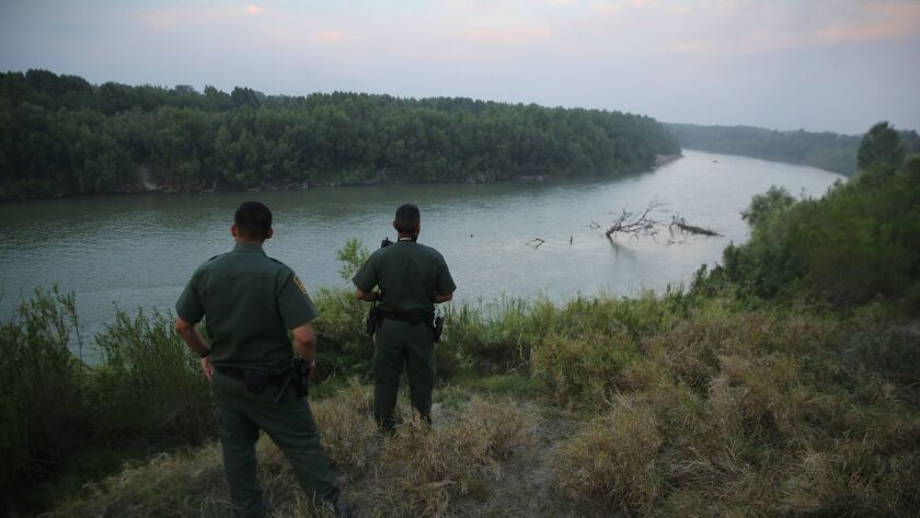 U.S. Border Patrol agents look for immigrants crossing the Rio Grande from Mexico to the United States.