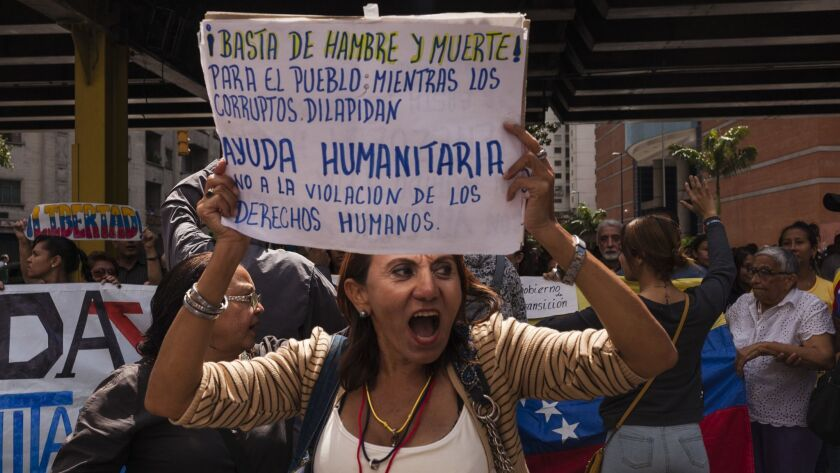 """People gather in Caracas, Venezuela, to support opposition leader Juan Guaido on Jan. 30, 2019. The sign reads: """"Enough with hunger and death! For the people while the corrupt squander. Humanitarian aid. No to the violation of human rights."""""""