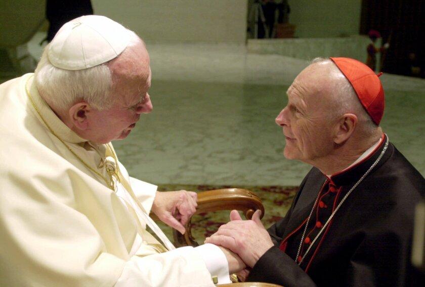 Cardinal Theodore Edgar McCarrick shakes hands with Pope John Paul II in 2001.
