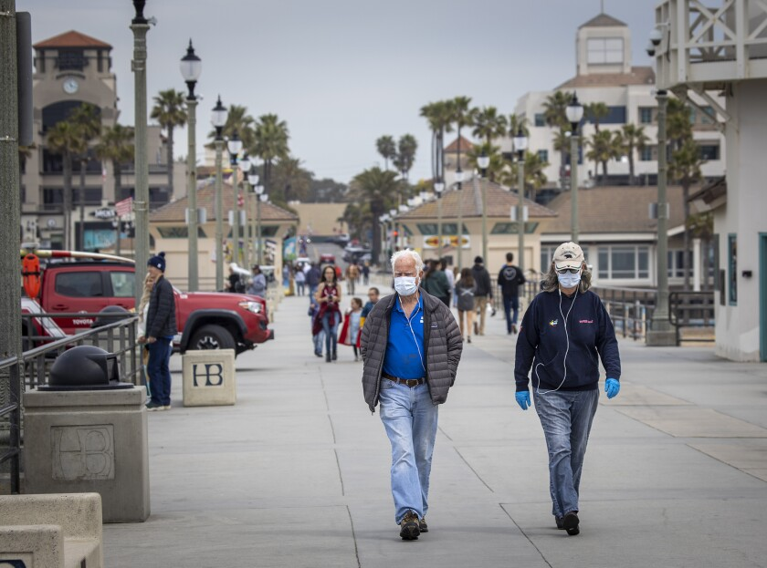 Dr. Dallas Weaver, and his wife, Janet Weaver, of Huntington Beach, wear their reusable protective masks and gloves that they will place in the oven and heat up to 160-degrees after their return from walking on the Huntington Beach pier amid coronavirus pandemic restrictions.