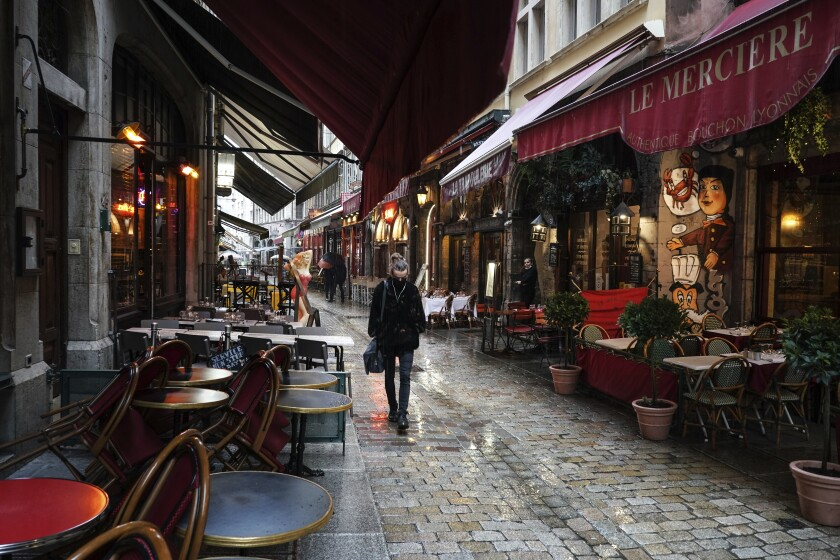 FILE - In this Oct. 2, 2020 file photo, a woman walks by empty restaurants in the center of Lyon, central France. France is expected Thursday April 15, 2021, to pass the grim milestone of 100,000 COVID-19 deaths, after a year of hospital tensions, on-and-off lockdowns and personal loss that have left families nationwide grieving the pandemic's unending, devastating toll. (AP Photo/Laurent Cipriani, File)