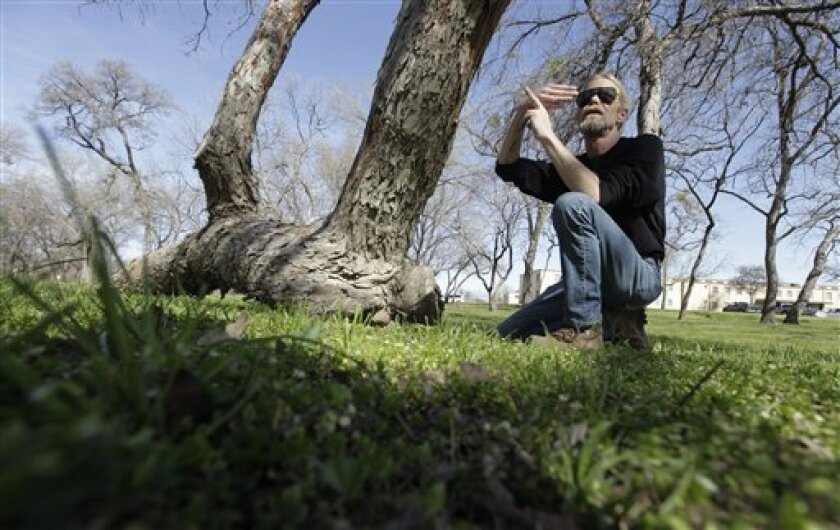 In this Feb. 23, 2012 photo, arborist Steve Houser talks about a Native American marker tree, left, in Dallas.  The pecan tree, more than 300 years old, stands out from the others in a forested area of Dallas, a 25-foot segment of its trunk slightly bowed and running almost parallel to the ground b