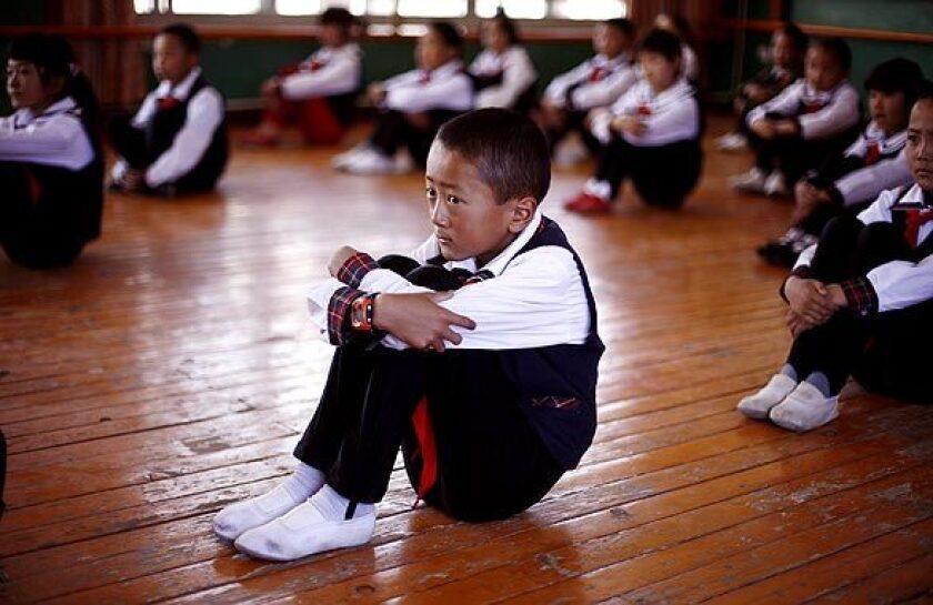 Tibetan students sit in dance class at school in Tibet