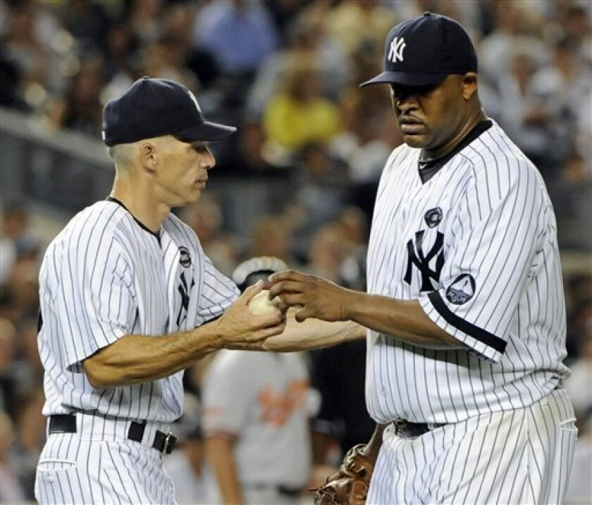 New York Yankees manager Joe Girardi, left, takes the ball from pitcher CC Sabathia as he leaves the baseball game during the seventh inning against the Baltimore Orioles on Tuesday, Sept. 7, 2010, at Yankee Stadium in New York. (AP Photo/Bill Kostroun)