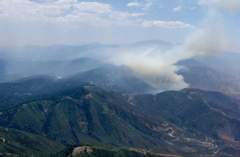 An aerial view of thick smoke rising among green mountains
