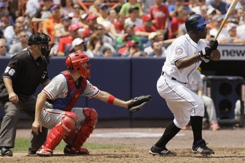 New York Mets' Carlos Delgado, right, follows through on a hit to left field as Philadelphia Phillies catcher Chris Coste and home plate umpire Eric Cooper look on during the eighth inning in Major League Baseball action Thursday, July 24, 2008 at Shea Stadium in New York. Robinson Cancel and David Wright scored on the play. The Mets won 3-1. (AP Photo/Julie Jacobson)