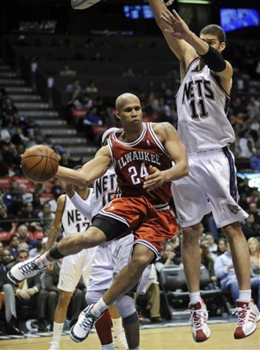 Milwaukee Bucks' Richard Jefferson, left, looks to pass the ball as New Jersey Nets' Brook Lopez defends during the fourth quarter of an NBA basketball game Tuesday, Feb. 3, 2009, in East Rutherford, N.J. Jefferson led all scorers with 27 points but the Nets beat the Bucks 99-85. (AP Photo/Bill Kostroun)