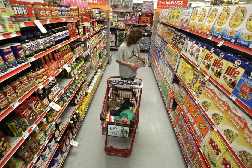 FILE - In this Dec. 14, 2010, file photo, Alicia Ortiz shops through the cereal aisle as her daughter Aaliyah Garcia catches a short nap in the shopping cart at a Family Dollar store in Waco, Texas. Up and down supermarket aisles, rows of perfectly placed products reflect calculated deliberations a