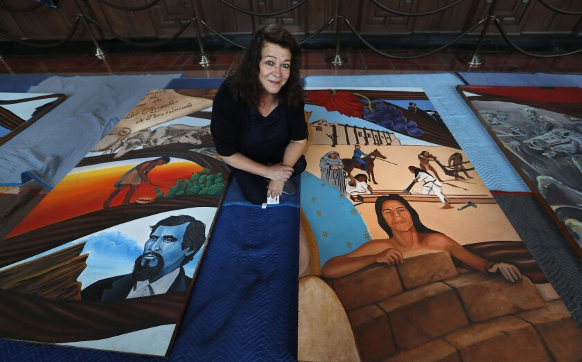 """Barbara Carrasco with sections of her mural, """"L.A. History: A Mexican Perspective,"""" as it was being installed at Union Station in L.A. in 2017."""