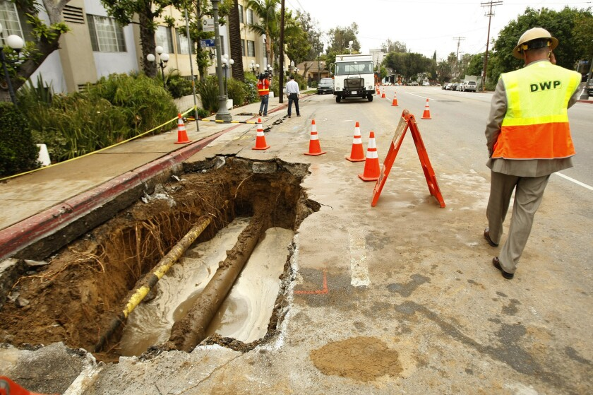 A Department of Water and Power worker is seen by a hole created by a 12-inch cast iron water main break.