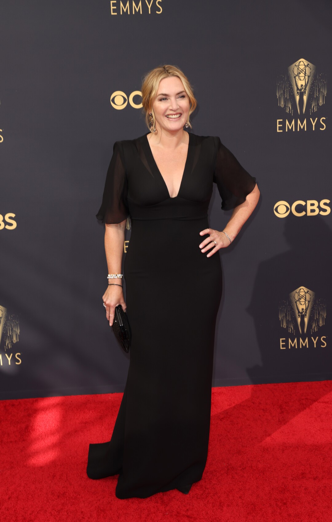 Kate Winslet in a long dark V-neck gown on the red carpet.