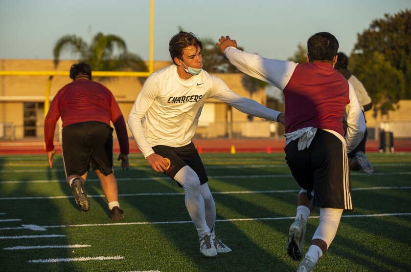 Estancia High School quarterback Cameron Knickerbocker works on running drills with running back Beto Sotomayor.