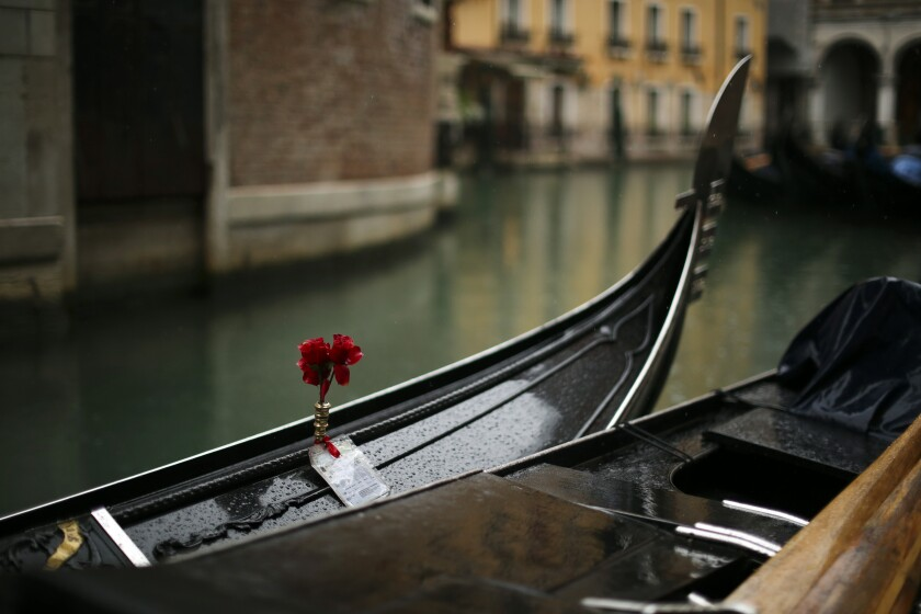 """Gondolas are parked on a rainy day in Venice, Sunday, March 1, 2020. Venice in the time of coronavirus is a shell of itself, with empty piazzas, shuttered basilicas and gondoliers idling their days away. The cholera epidemic that raged quietly through Venice in Thomas Mann's fictional """"Death in Venice"""" has been replaced by a real life fear of COVID-19. (AP Photo/Francisco Seco)"""