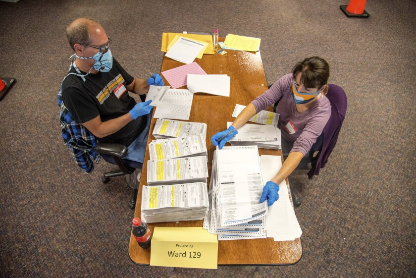Election workers Jeff and Lori Lutzka, right, process absentee ballots at Milwaukee's central count facility.