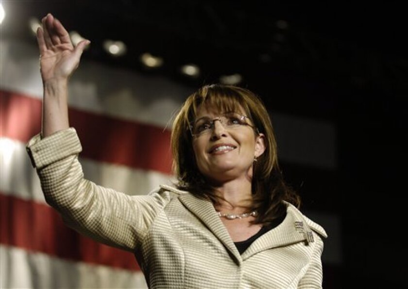 In this Dec. 1, 2008 file photo, Alaska Gov. Sarah Palin, center, waves to a crowd during a campaign stop for Sen. Saxby Chambliss, R-Ga, in Savannah, Ga. Palin has added to her financial disclosure forms two free trips that she took nearly two years ago but failed to report. (AP Photo/Stephen Morton, File)