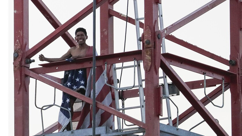 A man holds emergency personnel at bay as he descends a construction crane carrying a U.S. flag.