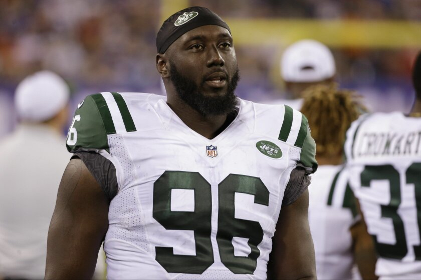 FILE - In this Saturday, Aug. 29, 2015 file photo, New York Jets defensive end Muhammad Wilkerson (96) walks the sidelines during the second half of a preseason NFL football game against the New York Giants in East Rutherford, N.J. The New York Jets have signed Muhammad Wilkerson to a five-year contract extension, beating the deadline after which the Pro Bowl defensive end would have had to play this season under the franchise tag amount of $15.7 million, Friday, July 15, 2016. (AP Photo/Seth Wenig, File)